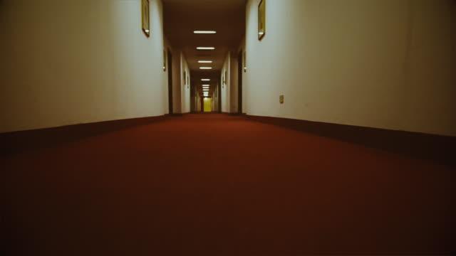 pov perspective into a dark hotel corridor: spooky themes - lobby video stock e b–roll