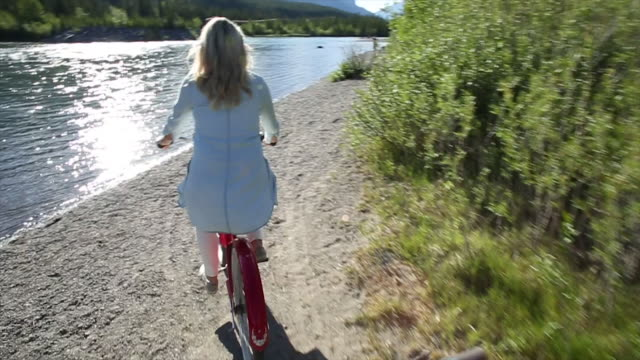 POV perspective of woman riding cruiser bicycle onto river beach, mountains