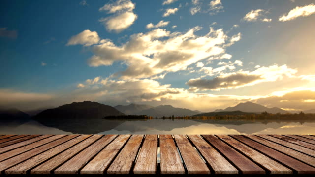 perspective wooden bridge on reflection lone tree in lake  wanaka background and flying cloud at new zealand - table stock videos & royalty-free footage