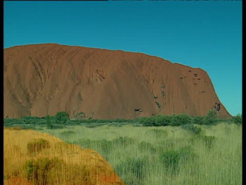 perspectives of uluru under clear blue sky australia - felswand stock-videos und b-roll-filmmaterial