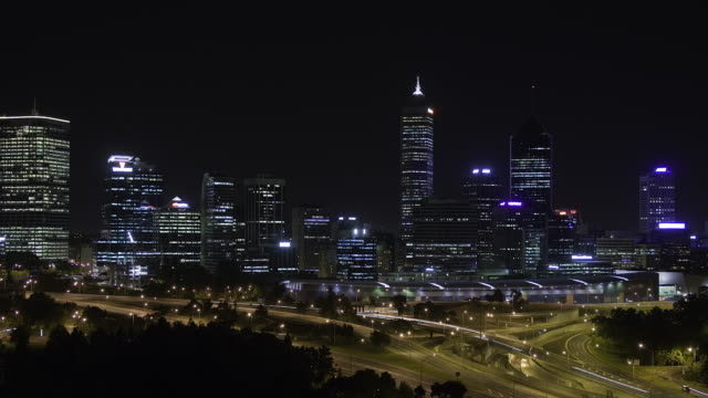 Perth central business district skyline at night seen behind peak hour traffic on freeways