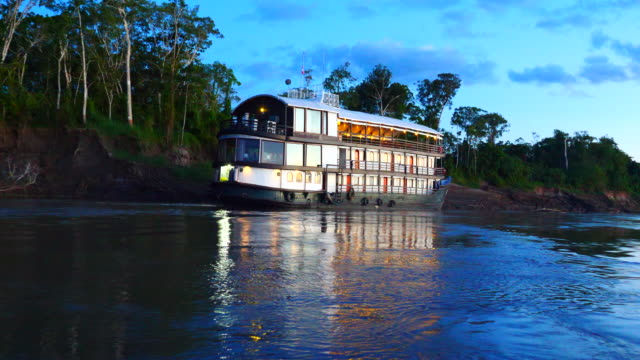 Peru, Amazon basin, La Amatista boat in the sunset with reflection, Pacaya Samiria National Reserve