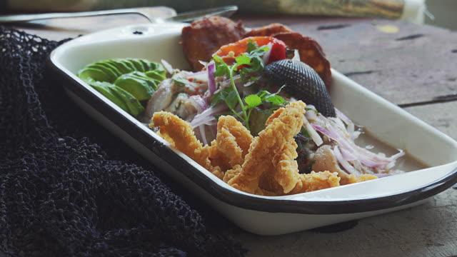 peruvian ceviche and squid chicharron - peruviano video stock e b–roll