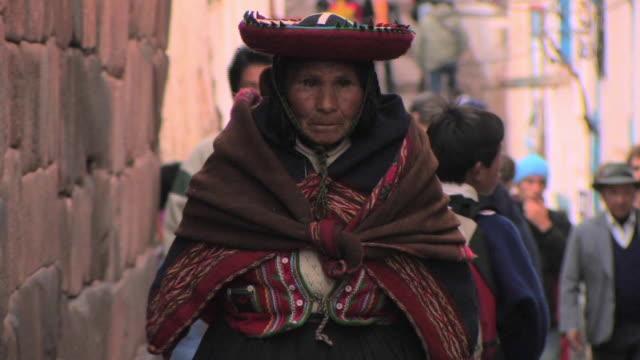 ms peruvian indian woman in traditional dress walking down street/ cuzco, peru - peruviano video stock e b–roll