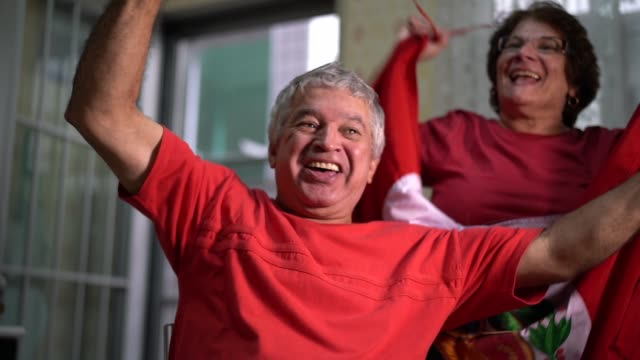 peruvian senior couple fan watching soccer game at home - peruvian ethnicity stock videos & royalty-free footage