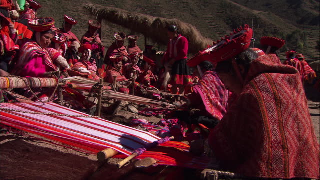 peruvian women in colorful traditional clothing weave fabric on a hillside. - traditional clothing stock videos & royalty-free footage