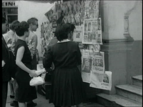 peruvians buy and look at newspapers about jfk's assassination newspaper headlines peruvians react to jfk assassination on november 29 1963 in lima... - attentat auf john f. kennedy stock-videos und b-roll-filmmaterial