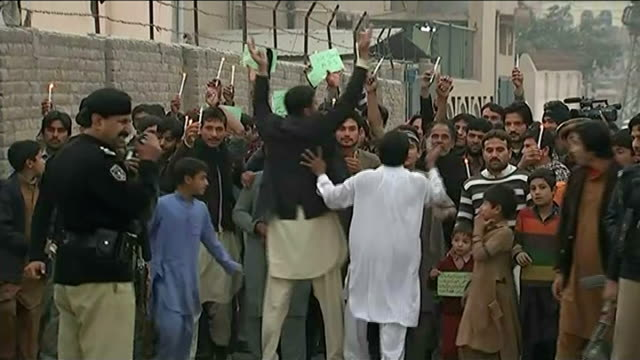 funerals of victims / political response protesters along people holding up candles and 'we stand aps' placards - peshawar video stock e b–roll