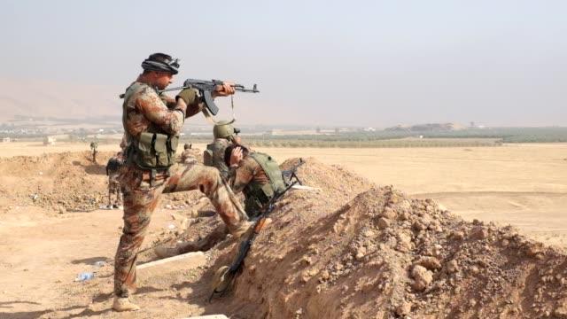stockvideo's en b-roll-footage met peshmerga fighter shoot his gun against deash in bashik on october 27 2016 - isis