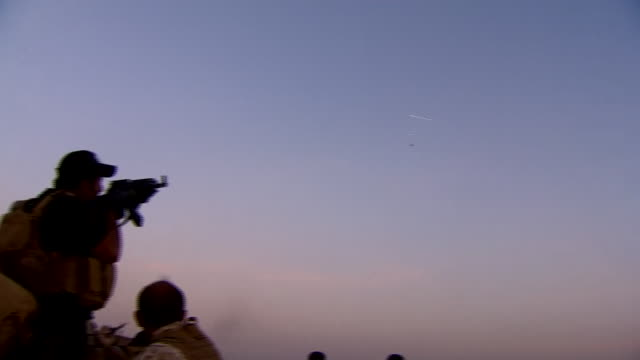 peshmerga fighters attempting to shoot down an islamic state drone flying overhead - isis stock-videos und b-roll-filmmaterial
