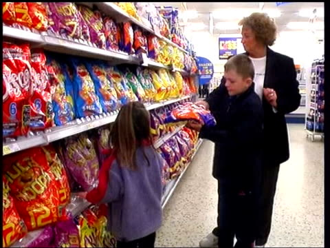 pester power of snack advertisers; lib child taking bumper bag of crisps from mother in supermarket & putting them into shopping trolley - snack stock videos & royalty-free footage