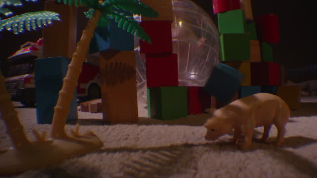 ms pet syrian hamster rolls exercise ball to camera and knocks down bricks in childs dark bedroom - toy block stock videos and b-roll footage