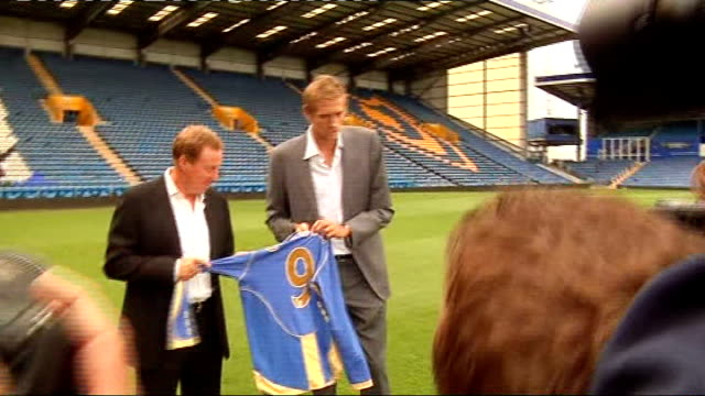 peter crouch crouch and redknapp hold up portsmouth fc football shirt on pitch with crouch's name on back in front of press photographers - ハリー レッドナップ点の映像素材/bロール