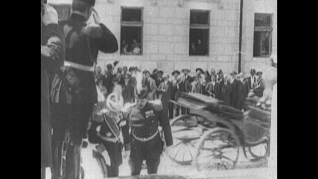 Peter I of Serbia is assisted up stairs as a horsedrawn carriage pulls away