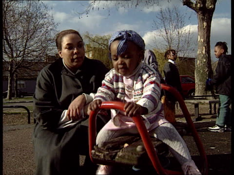 peter lilley threatens single-mother benefits; england: london: kilburn: tanya lee as lifts kyra onto a rocking-horse style ride: tanya lee: kyra... - single mother stock videos & royalty-free footage