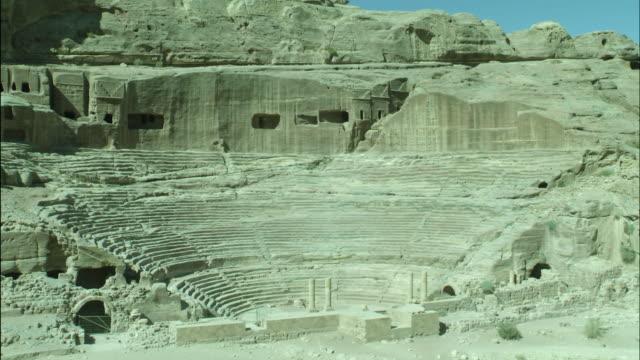 petra archaeological site and amphitheatre, pan away to rocky desert surrounds, jordan - アラバ砂漠点の映像素材/bロール