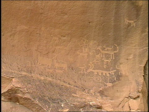 petroglyphs cover a rock face. - chaco canyon stock videos & royalty-free footage