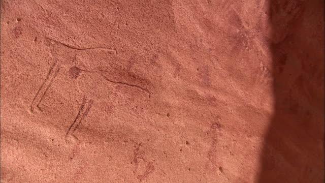 petroglyphs cover a rockface at gilf kebir in the sahara desert. - prehistoric art stock videos & royalty-free footage