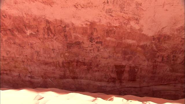 petroglyphs cover a sheer cliff at gilf kebir in the sahara desert. - prehistoric art stock videos & royalty-free footage