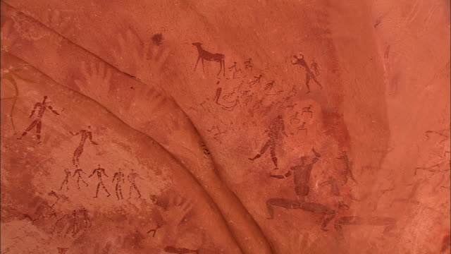 petroglyphs cover part of a rock wall in the desert. - sahara desert stock videos & royalty-free footage