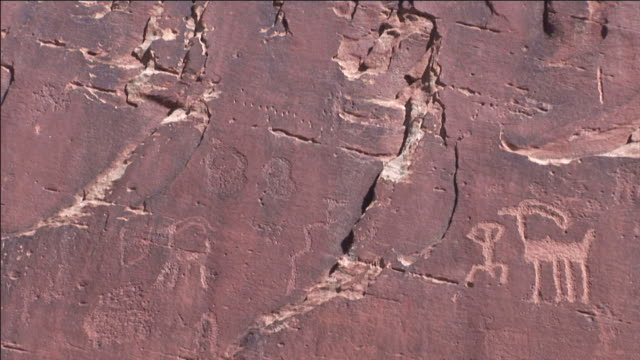 Petroglyphs decorate the face of a red rock canyon wall.