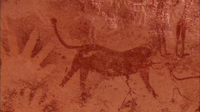 petroglyphs depict animals with long tails amid human figures. - prehistoric art stock videos & royalty-free footage