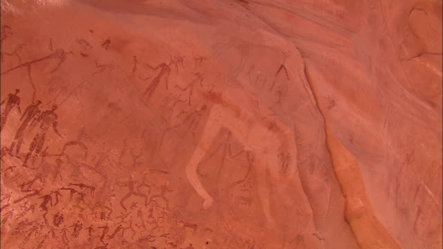petroglyphs of human figures cover a cliff at gilf kebir in the sahara desert. - cave painting stock videos & royalty-free footage