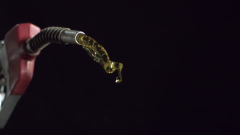cu slo mo petrol flowing from gas nozzle against black background / new jersey, usa - petrol stock videos & royalty-free footage