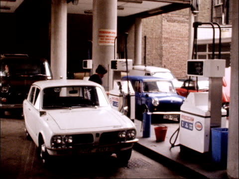 petrol prices reduced by shell and esso england london esso sign pull out rl to cars at pumps ms car filled cs nozzle in tank ms car filled cs shell... - price stock videos and b-roll footage