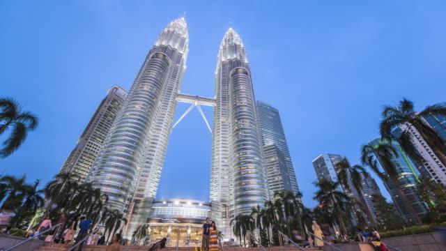 vídeos de stock, filmes e b-roll de ws la t/l petronas towers at dusk with tourists / kuala lumpur, selangor, malaysia - torres petronas