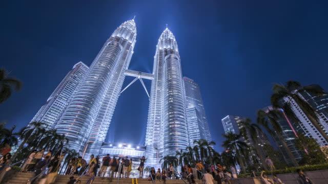 WS LA T/L Petronas Towers at dusk with tourists / Kuala Lumpur, Selangor, Malaysia