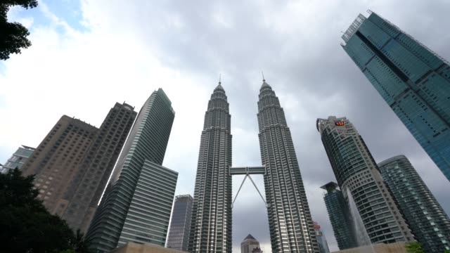 petronas türme von unten in kuala lumpur - 4k video - petronas twin towers stock-videos und b-roll-filmmaterial