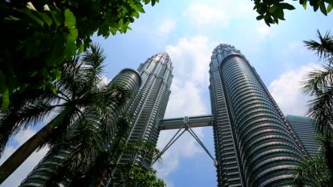 vídeos y material grabado en eventos de stock de torres petronas con palmeras y palm, kuala lumpur malaysia - acero inoxidable