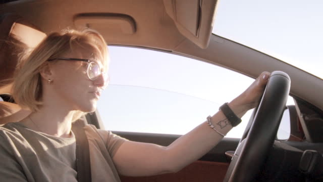 petty woman driving a car at sunset - seat belt stock videos & royalty-free footage