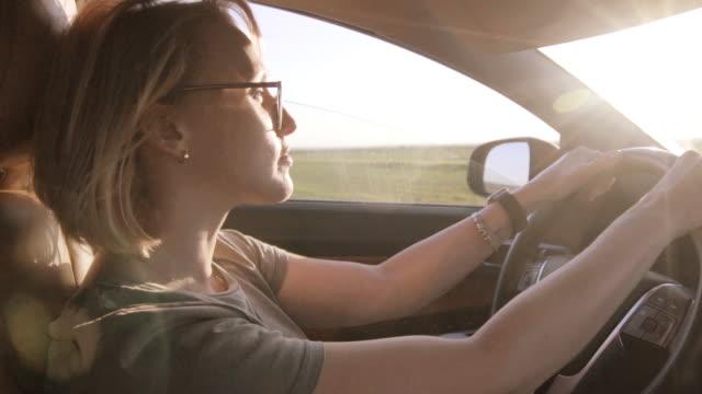 vidéos et rushes de femme de petite petite urne conduisant une voiture au coucher du soleil - lunette soleil