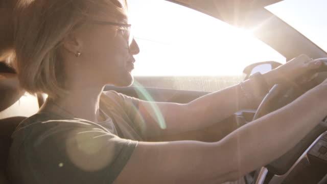vídeos y material grabado en eventos de stock de mujer mezquina conduciendo un coche al atardecer - transporte terrestre