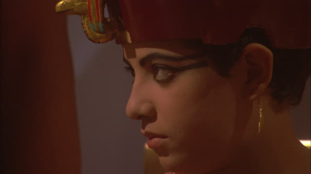 vidéos et rushes de a pharaoh wears makeup and a crown next to a man wearing a leopard skin robe. - prêtre