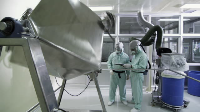 ws pharmaceutical mixer rotating, pharmaceutical manufacturers looking at clipboard / ratchathewi, bangkok, thailand - pharmaceutical manufacturing machine stock videos & royalty-free footage