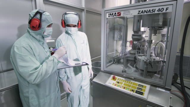 ws zi pharmaceutical pill press working, pharmaceutical manufacturer looking at clipboard / ratchathewi, bangkok, thailand - quality control stock videos & royalty-free footage
