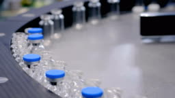 Pharmaceutical technology concept - conveyor belt with empty glass bottles