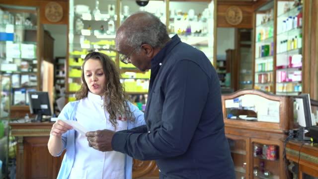 薬剤師の処方と年配の男性を支援 - 説明する点の映像素材/bロール