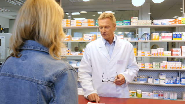 pharmacist assisting woman with medicine at store - pharmacy stock videos & royalty-free footage