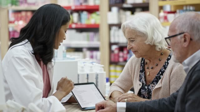 pharmacist discussing with couple on digital tablet - pharmacy stock videos & royalty-free footage