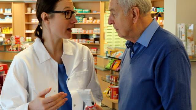 Pharmacist Explaining Medicine To Senior Man
