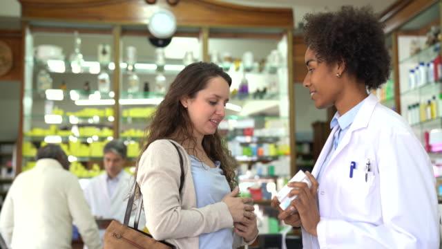 vídeos de stock, filmes e b-roll de farmacêutico explicando medicamentos a mulher na loja - farmácia
