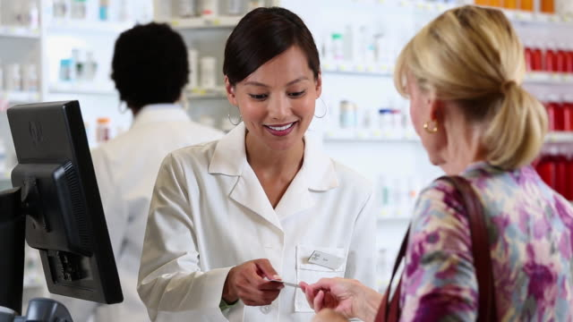 ms pan pharmacist filling prescription and talking to customer at pharmacy counter / richmond, virginia, usa - prescription medicine stock-videos und b-roll-filmmaterial