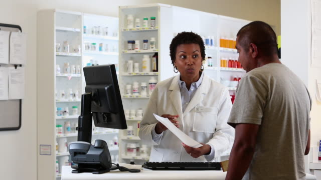 WS PAN Pharmacist Filling Prescription and Talking to Customer at Pharmacy Counter / Richmond, Virginia, USA