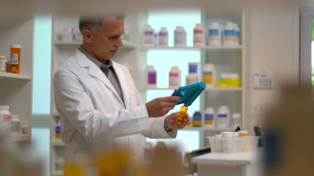stockvideo's en b-roll-footage met pharmacist filling prescription. - apotheker
