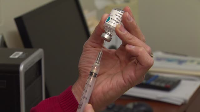 stockvideo's en b-roll-footage met wgn pharmacist filling up syringe with flu vaccine on september 26 2013 in chicago illinois - griepvaccin