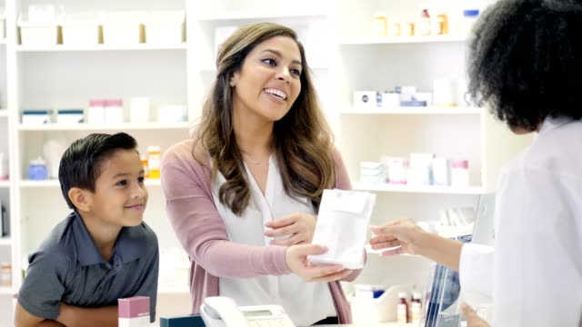 Pharmacist gives medication to mid adult woman